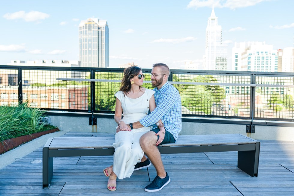 Local Love: 10 Best Places to Photograph in North Carolina - I'm Fixin' To - @mbg0112 | Best Places to Photography in North Carolina by popular N.C. lifestyle blog, I'm Fixin' To: image of a woman wearing a white jumpsuit and on a bench with her husband at The Rooftop at the Dillon in Raleigh, N.C.