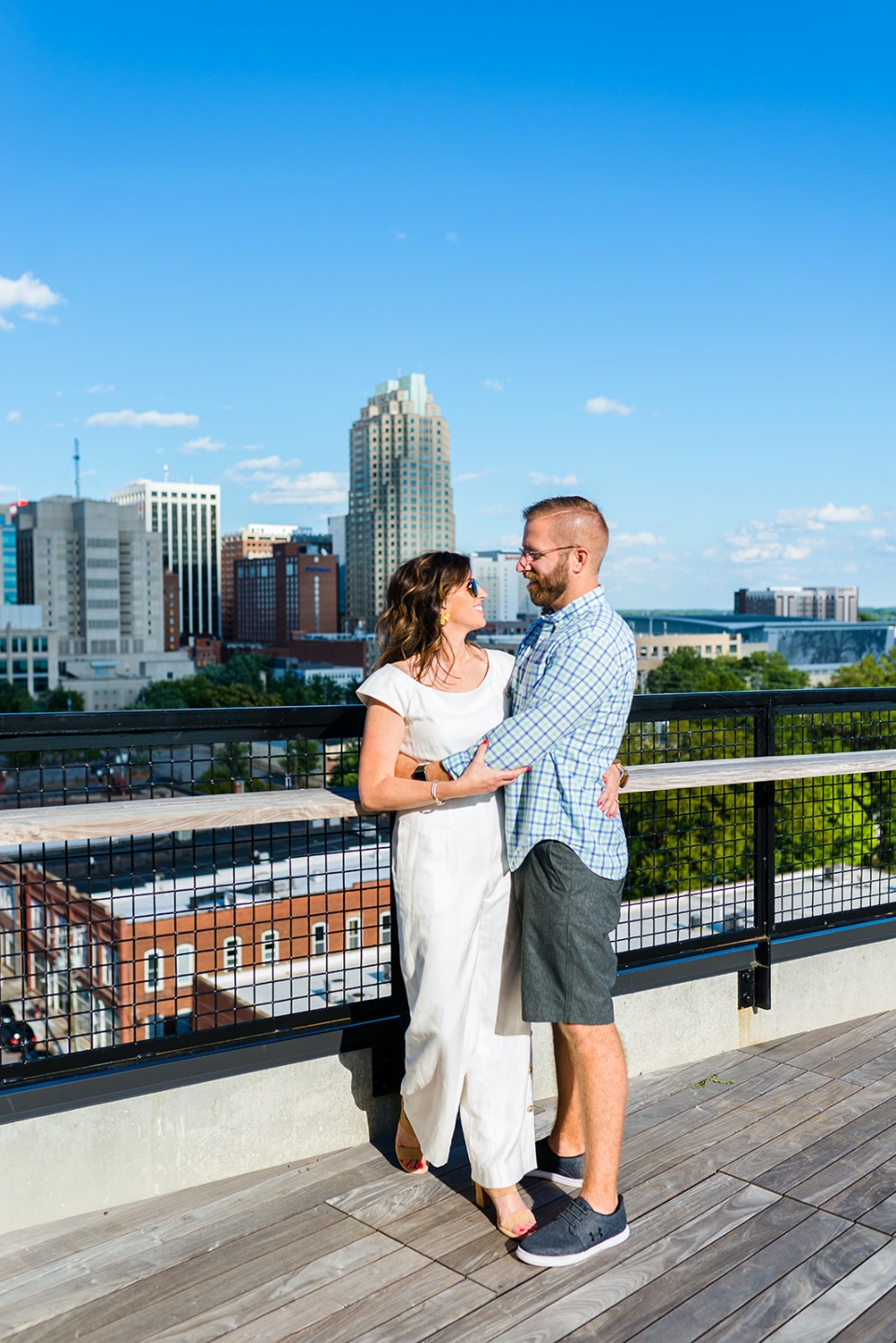 Local Love: 10 Best Places to Photograph in North Carolina - I'm Fixin' To - @mbg0112 | Best Places to Photography in North Carolina by popular N.C. lifestyle blog, I'm Fixin' To: image of a woman wearing a white jumpsuit and standing in the arms of her husband on The Rooftop at the Dillon in Raleigh, N.C.