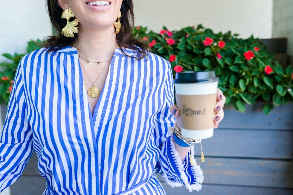 Civic Engagement by popular N.C. fashion blog, I'm Fixin' To: image of a woman wearing a blue and white stripe top, gold statement earrings, gold coin necklace, and a Etsy customized Vote necklace.