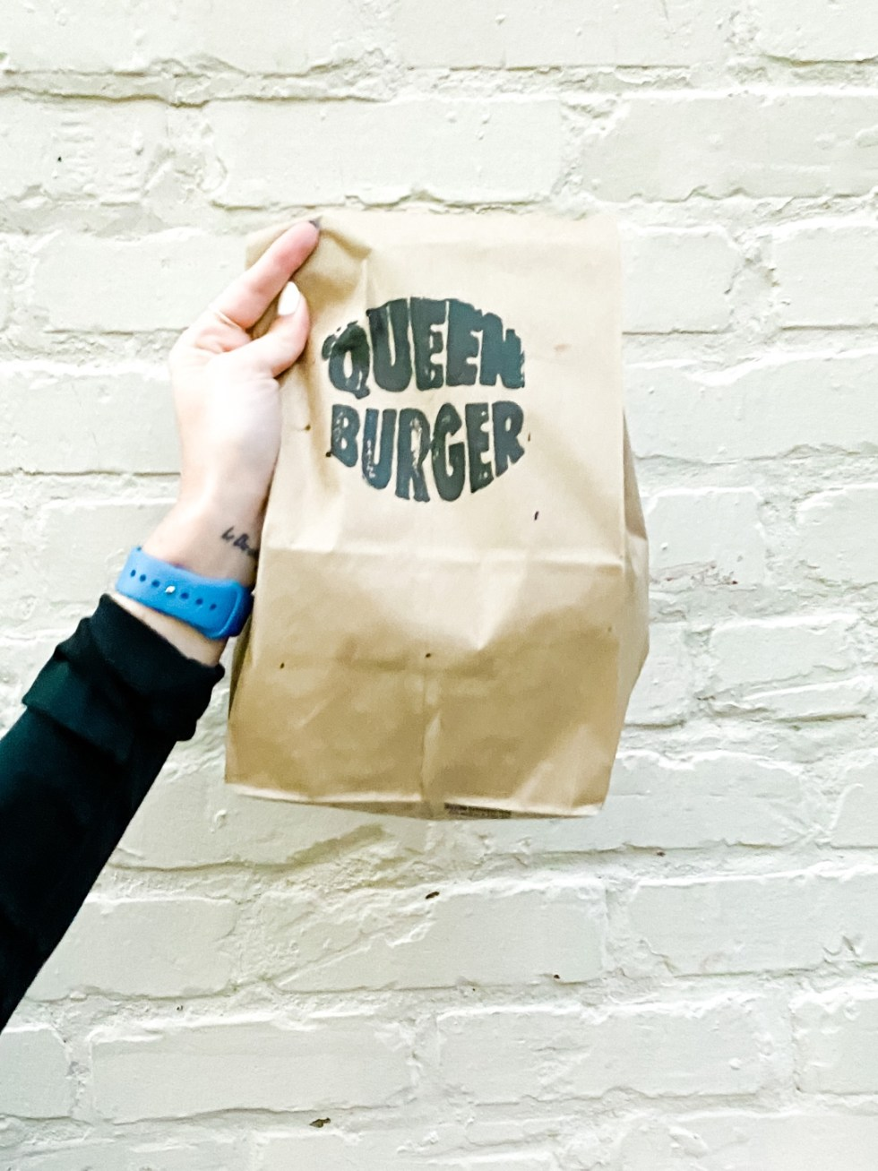 Date Night at the The Streetery in Downtown Durham - I'm Fixin' To - @mbg0112 |The Streetery in Downtown Durham by popular N.C. blog, I'm Fixin' To: image of a woman holding a Queen Burger bag.