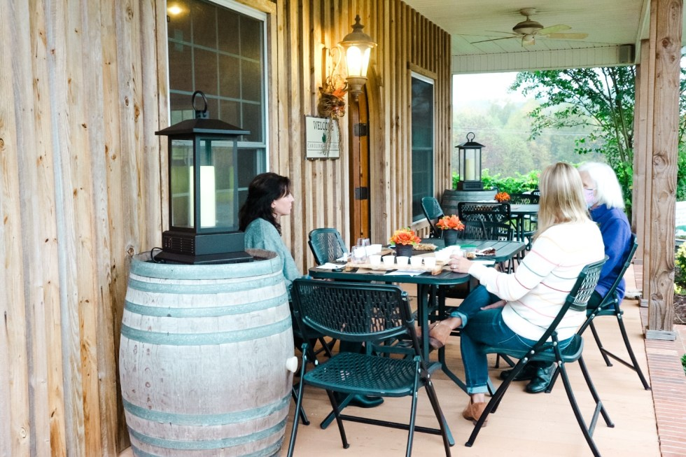 Western NC Wineries: 6 Wineries to Visit During your Next Girls' Weekend - I'm Fixin' To - @mbg0112 |Western NC Wineries by popular NC blog, I'm Fixin' To: image of three women sitting outside at Carolina Heritage vineyard and winery.