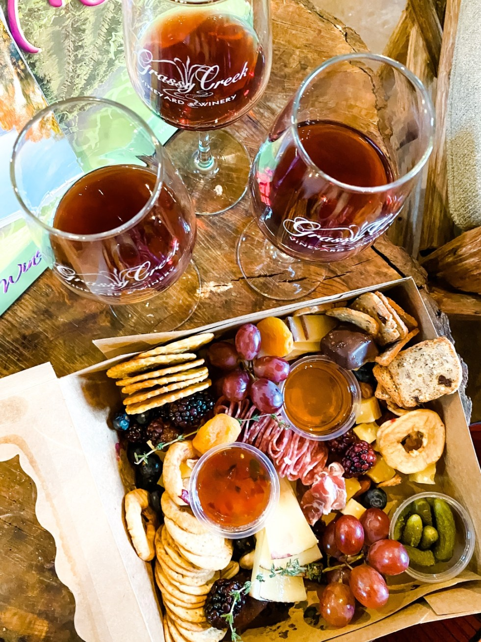 Western NC Wineries: 6 Wineries to Visit During your Next Girls' Weekend - I'm Fixin' To - @mbg0112 |Western NC Wineries by popular NC blog, I'm Fixin' To: image of glasses of red wine next to a charcuterie box.
