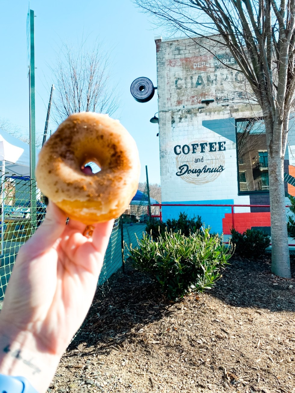 Christmas in Asheville: a Weekend Getaway During the Holidays - I'm Fixin' To - @imfixintoblog |Christmas in Asheville NC by popular NC lifestyle blog, I'm Fixin' To: image of a woman holding a doughnut at Cedric's Tavern.