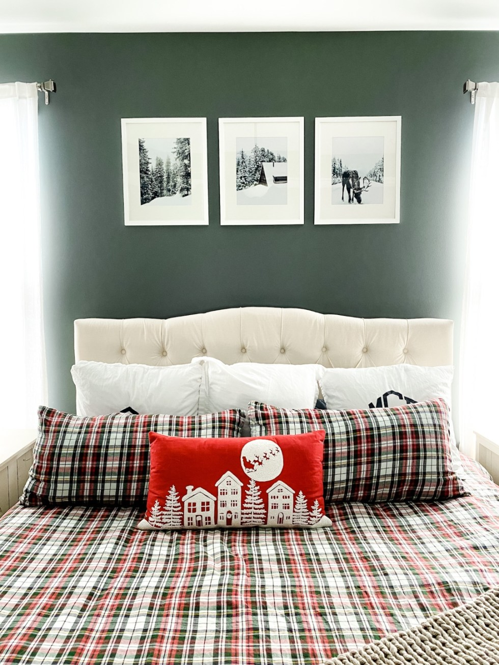 Home Decor: 7 Winter Art Prints for your Gallery Wall - I'm Fixin' To - @imfixintoblog |Winter Art Prints by popular NC life and style blog, I'm Fixin' To: image of three winter art prints hanging above a bed with red, white, and green plaid bedding and a white tuft headboard.