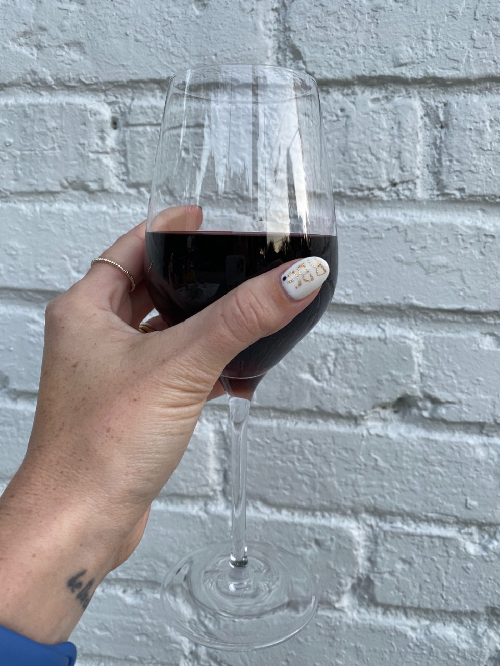 NC Favorites: 5 Warm Restaurants with Patios in the Triangle - I'm Fixin' To - @mbg0112 |Restaurants with Patios in the Triangle by popular NC lifestyle blog, I'm Fixin' To: image of a woman holding a glass of red wine.