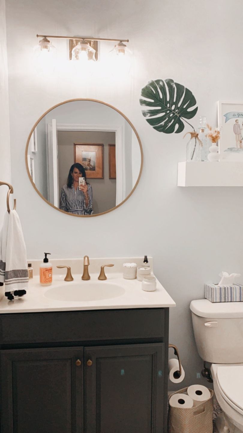 3 Years in Our Ranch: Home Updates - I'm Fixin' To - @imfixintoblog |Home Updates by popular NC life and style blog, I'm Fixin' To: image of a bathroom with a round mirror, black vanity, modern gold light fixture, gold faucet, and white floating shelf.