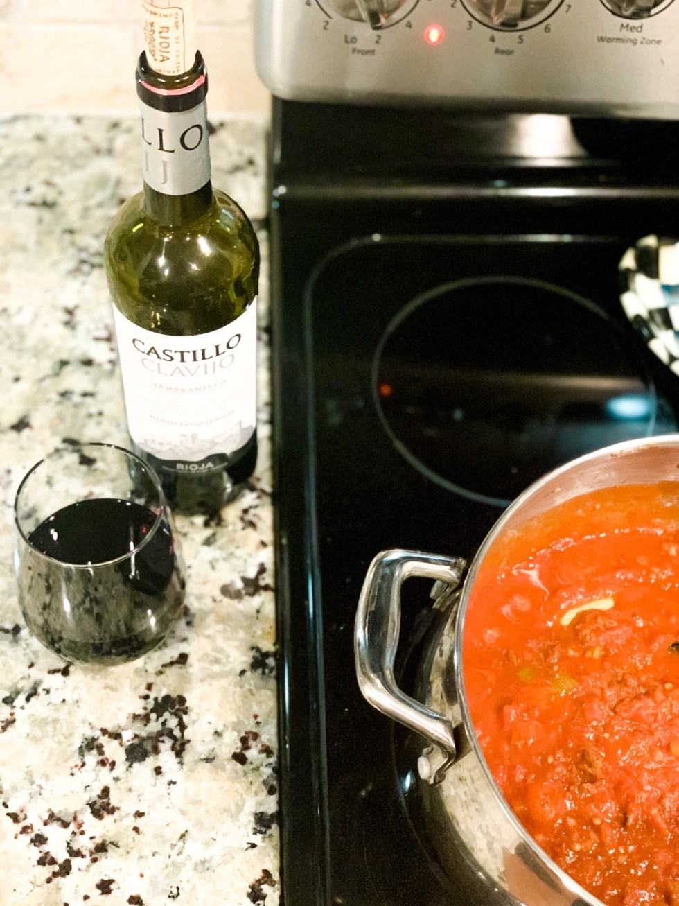 20 Moments I am Grateful for in 2020 - I'm Fixin' To - @imfixintoblog |Moments to be Grateful for by popular NC lifestyle blog, I'm Fixin' To: image of a bottle of red wine and a cup of red wine next to a pot of spaghetti sauce.