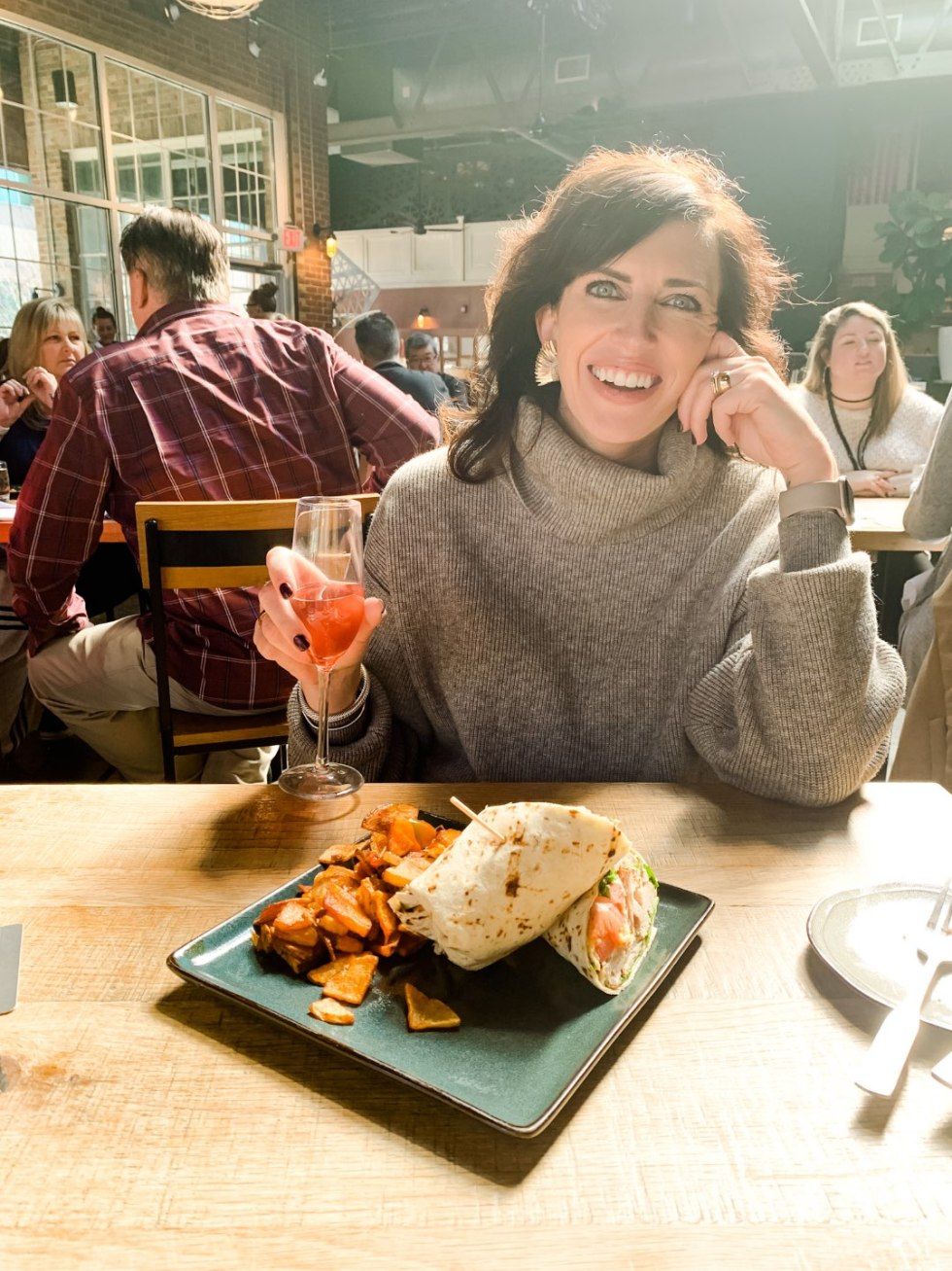 20 Moments I am Grateful for in 2020 - I'm Fixin' To - @imfixintoblog |Moments to be Grateful for by popular NC lifestyle blog, I'm Fixin' To: image of a woman wearing a grey turtleneck sweater and sitting in front of a plate of food at a restaurant.