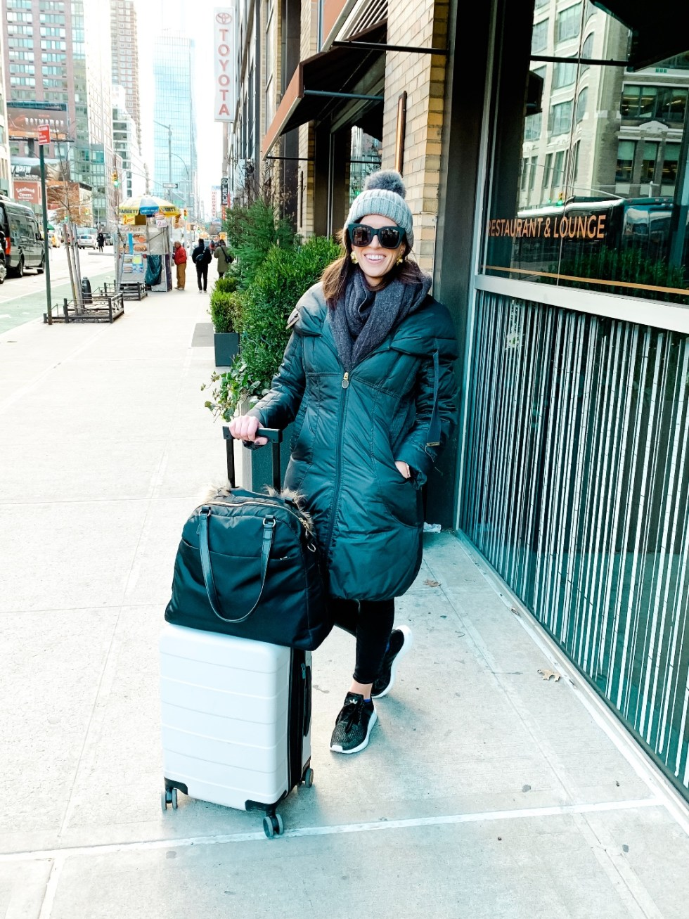 9 Hotels on My Radar - I'm Fixin' To - @imfixintoblog |Hotels to Visit by popular NC travel blog, I'm Fixin' To: image of a woman wearing a long black coat and grey pom beanie and standing outside next to her white rolling suitcase and large black duffle bag.