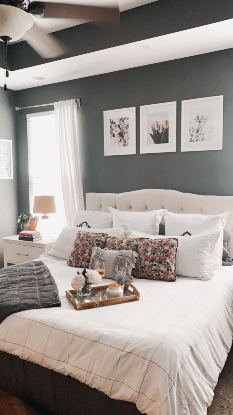 How to Make Your Home Cozy by popular NC life and style blog, I'm Fixin' To: image of a bedroom with a bed with a white tuft headboard ad white bedding, floral print artwork, white night stands, white curtains, grey walls, and a serving tray set with a vase of flowers and a candle.
