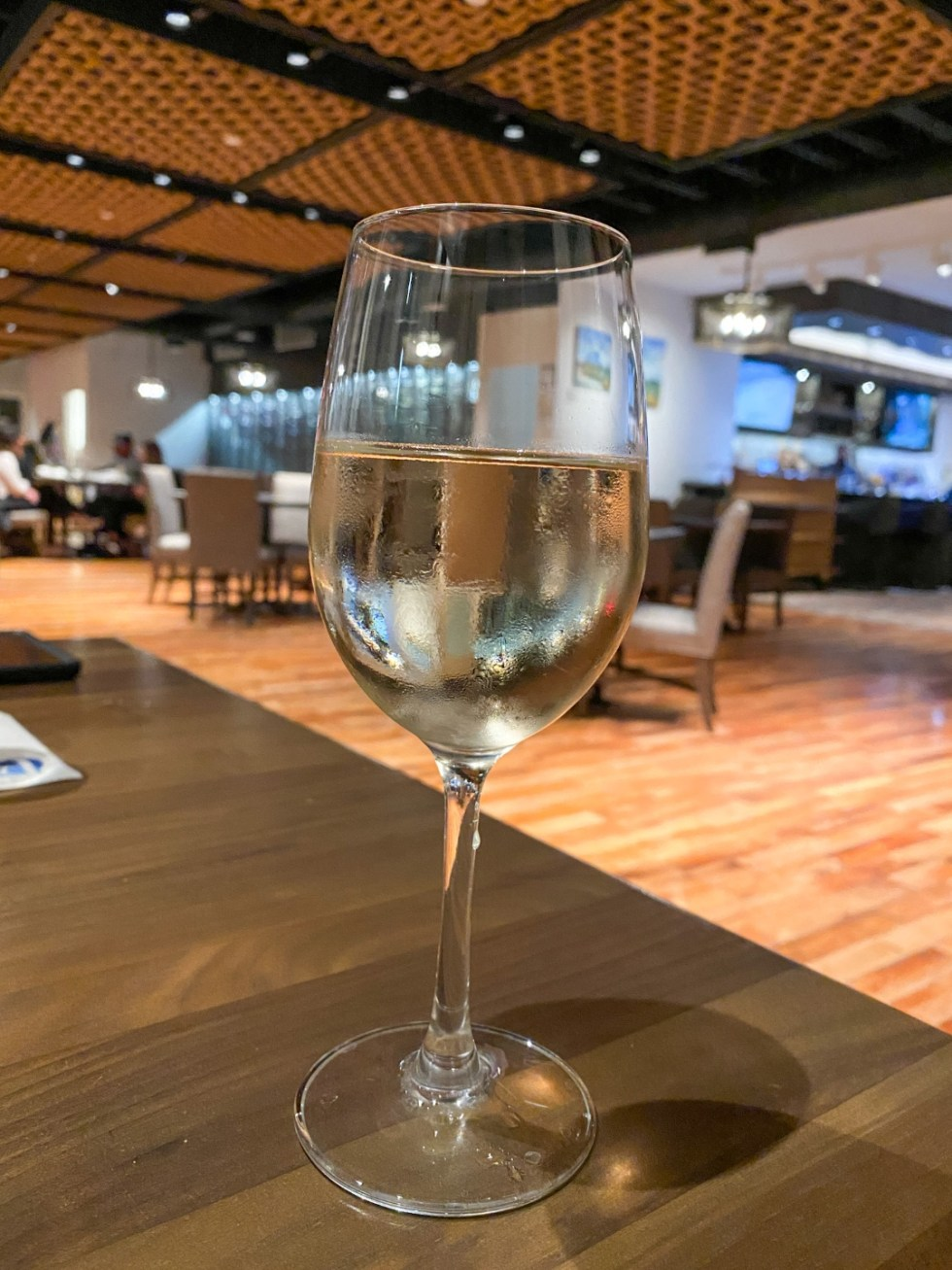 Weekend Travel: The Best Things to Do in Beaufort NC in 48 Hours - I'm Fixin' To - @imfixintoblog |Things to Do in Beaufort NC by popular NC travel blog, I'm Fixin' To: image of a glass of white wine.