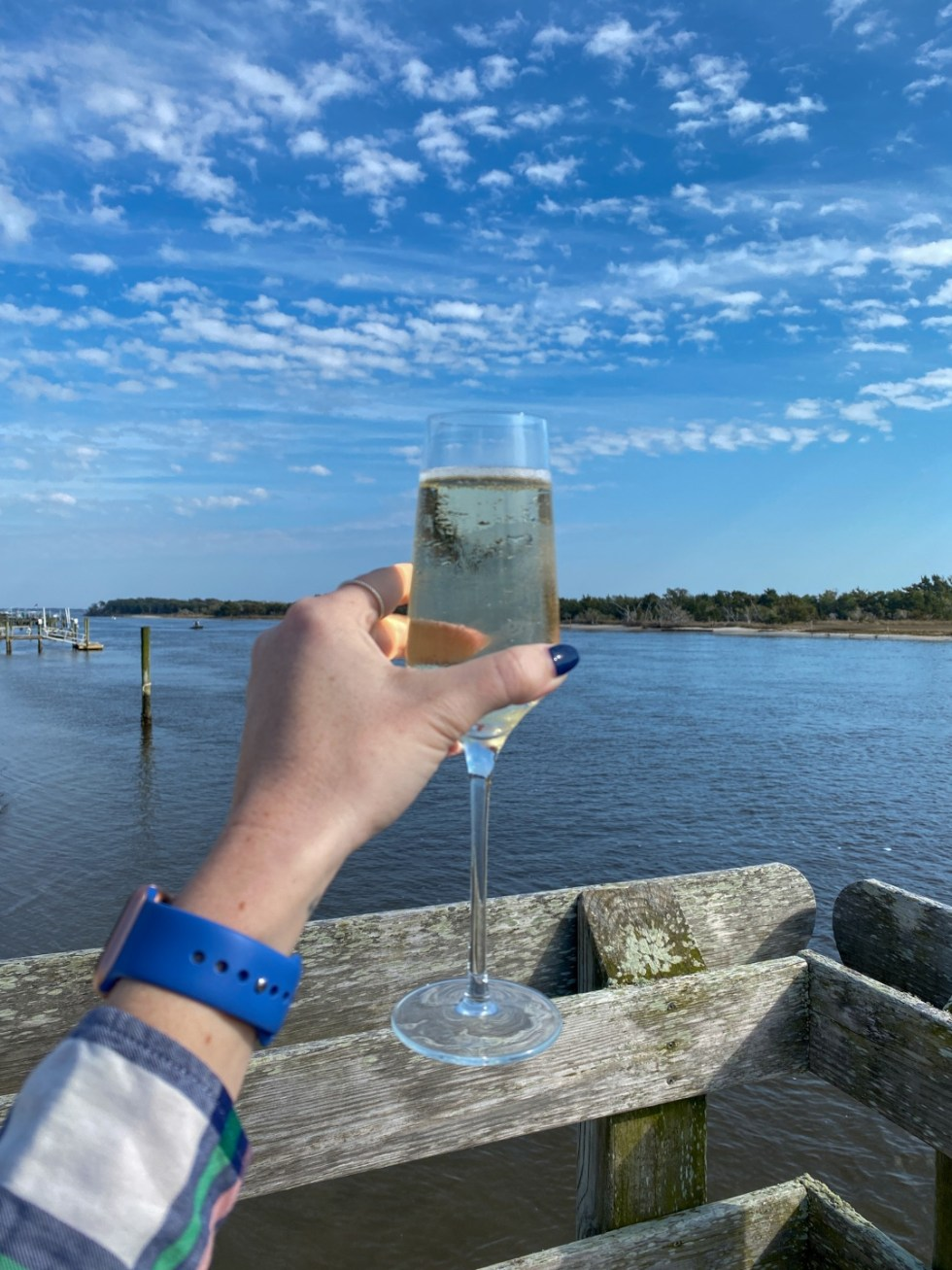 Weekend Travel: The Best Things to Do in Beaufort NC in 48 Hours - I'm Fixin' To - @imfixintoblog |Things to Do in Beaufort NC by popular NC travel blog, I'm Fixin' To: image of a woman holding a glass of white wine.