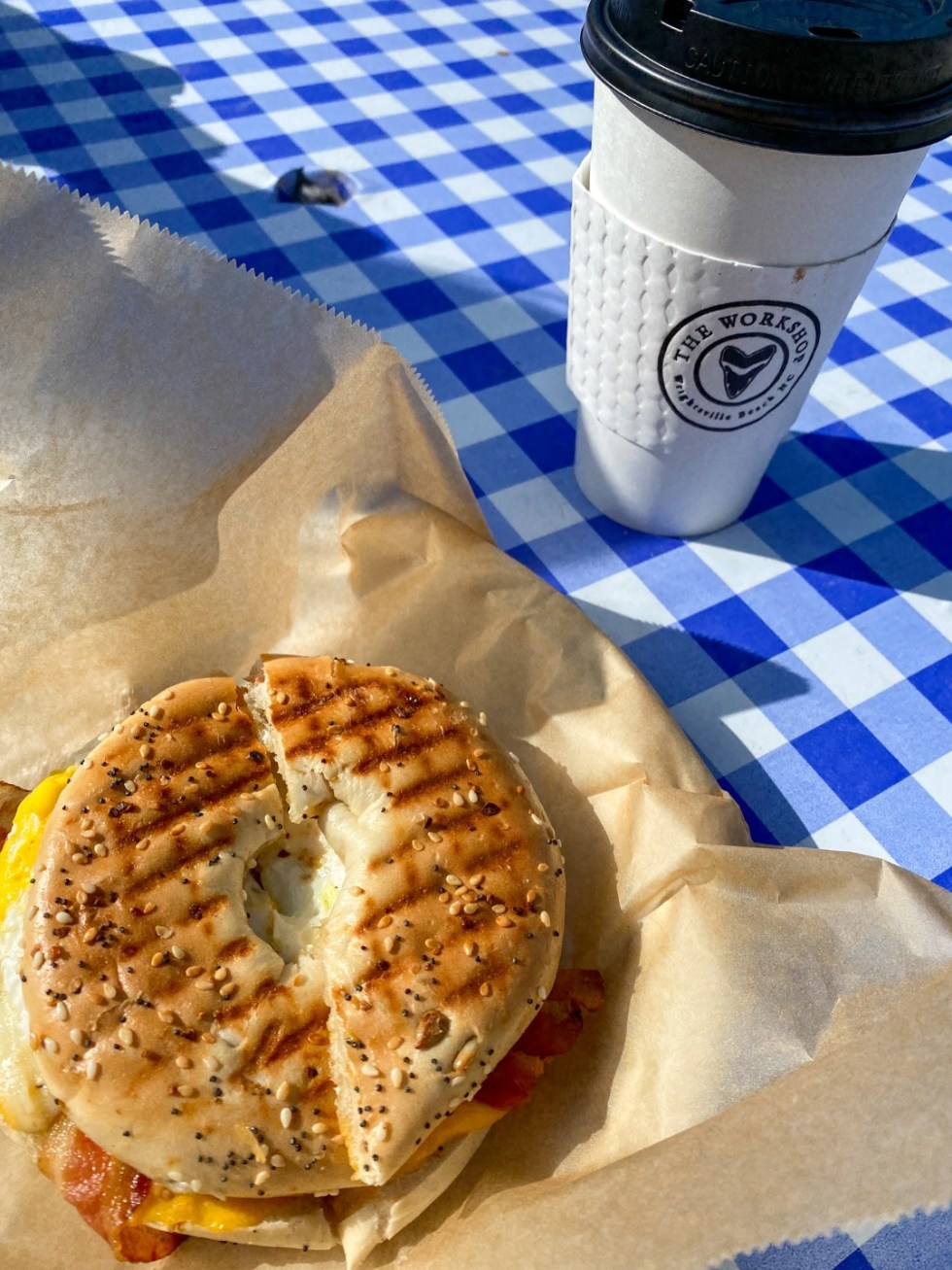 A Spring Weekend in Wilmington, NC: the Best Things to Do - I'm Fixin' To - @imfixintoblog |Weekend in Wilmington by popular NC travel blog, I'm Fixin' To: image of a bagel sandwich next to a The Workshop coffee cup.