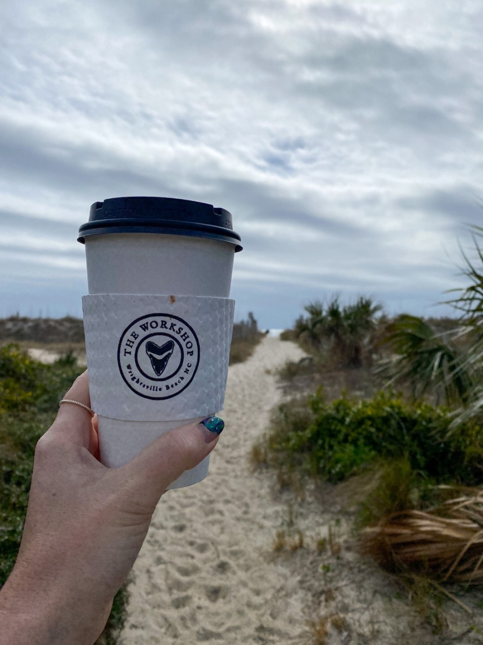 A Spring Weekend in Wilmington, NC: the Best Things to Do - I'm Fixin' To - @imfixintoblog |Weekend in Wilmington by popular NC travel blog, I'm Fixin' To: image of a woman holding a cup of coffee at Wrightsville beach.