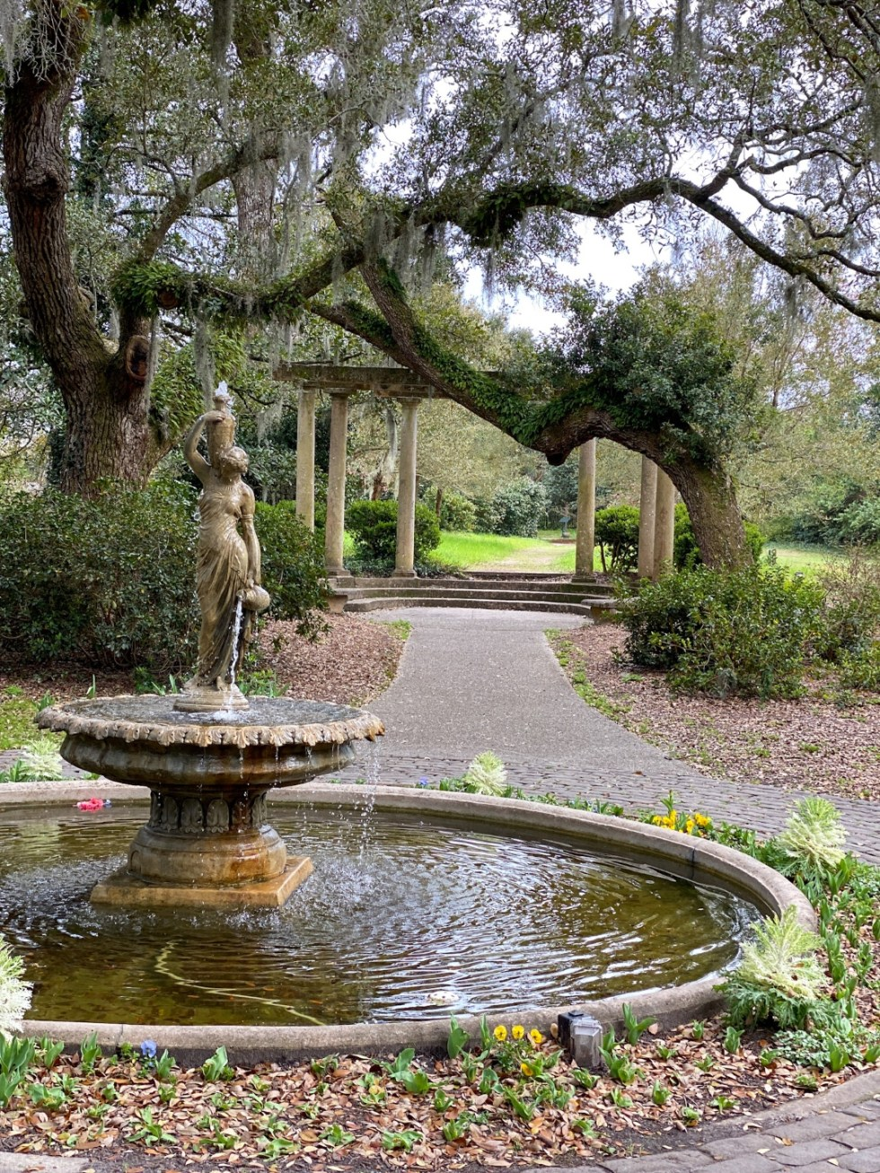 A Spring Weekend in Wilmington, NC: the Best Things to Do - I'm Fixin' To - @imfixintoblog |Weekend in Wilmington by popular NC travel blog, I'm Fixin' To: image of oak trees and a water fountain feature in Airlie Gardens.