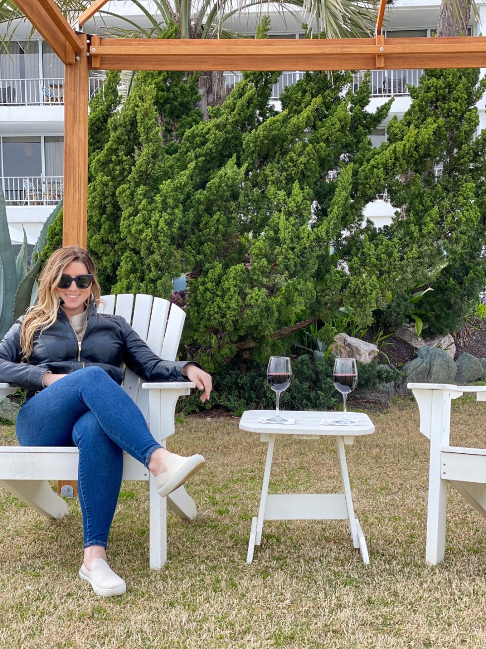 A Spring Weekend in Wilmington, NC: the Best Things to Do - I'm Fixin' To - @imfixintoblog |Weekend in Wilmington by popular NC travel blog, I'm Fixin' To: image of a woman sitting in a white wooden lounge chair next to a white end table holding two glasses of red wine.