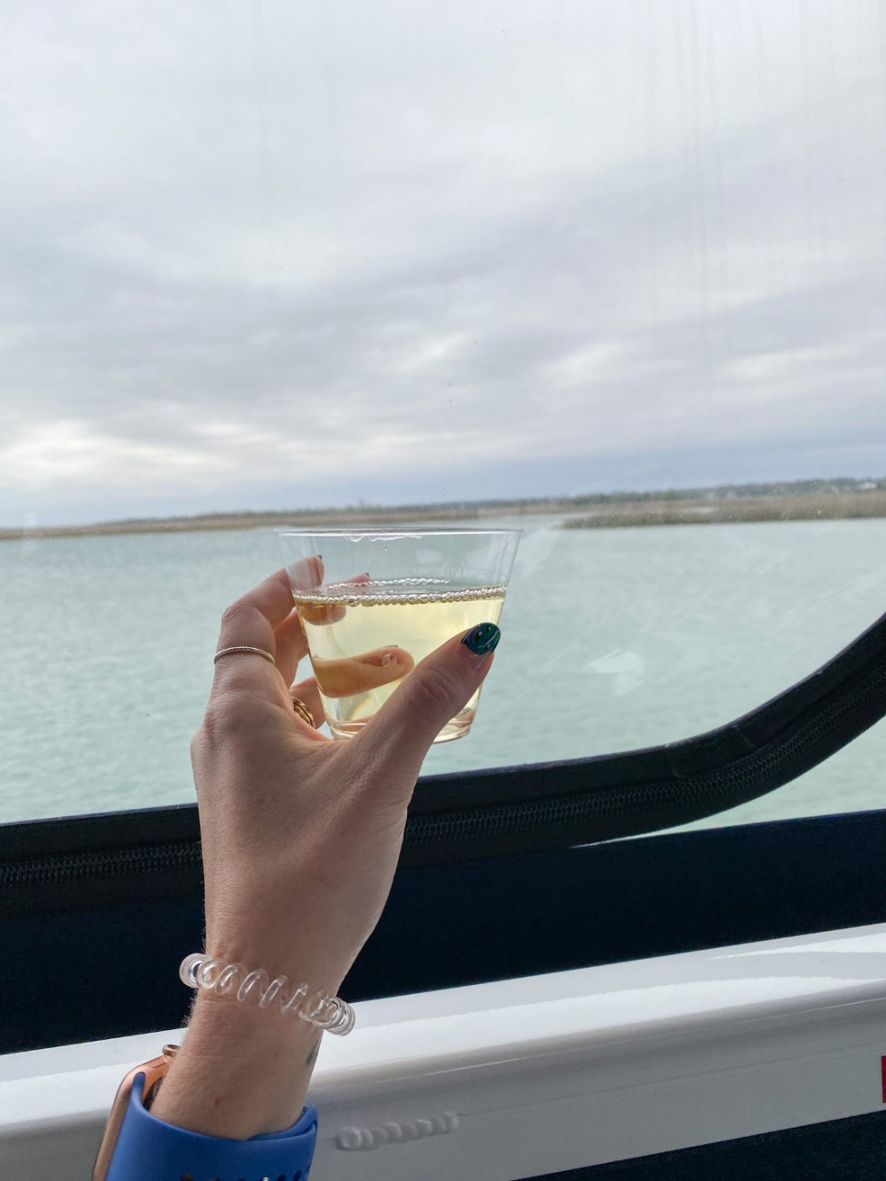 A Spring Weekend in Wilmington, NC: the Best Things to Do - I'm Fixin' To - @imfixintoblog |Weekend in Wilmington by popular NC travel blog, I'm Fixin' To: image of a woman holding a glass filled with white wine.