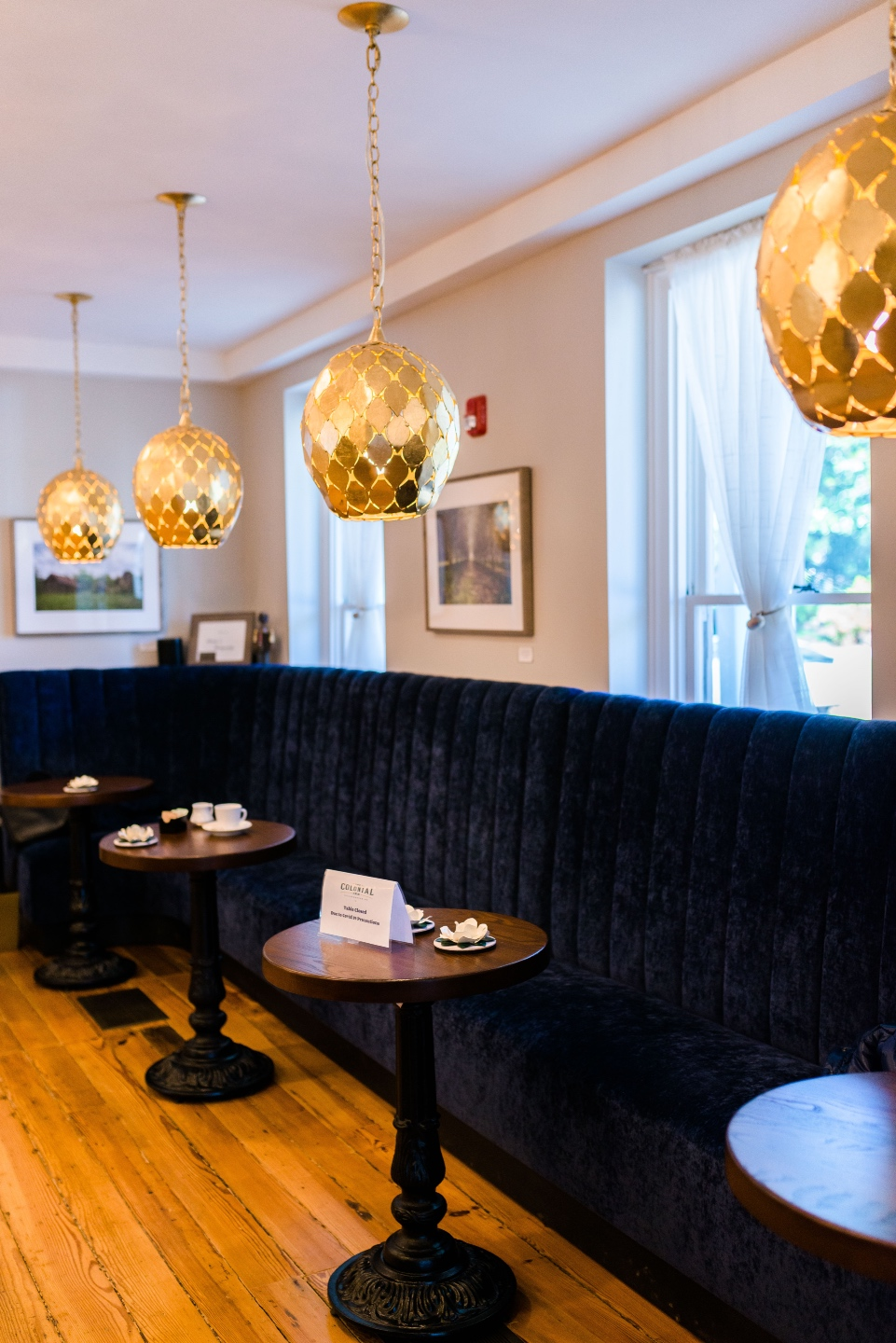 Places to Stay: The Colonial Inn in Hillsborough NC - I'm Fixin' To - @imfixintoblog |The Colonial Inn Hillsborough NC by popular NC travel blog, I'm Fixin' To: image of a black velvet bench, gold pendant lights, and round tables set with espresso cups.