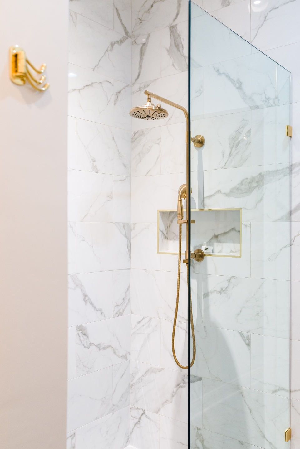 Places to Stay: The Colonial Inn in Hillsborough NC - I'm Fixin' To - @imfixintoblog |The Colonial Inn Hillsborough NC by popular NC travel blog, I'm Fixin' To: image of a walk-in shower with marble tiles and gold shower head.