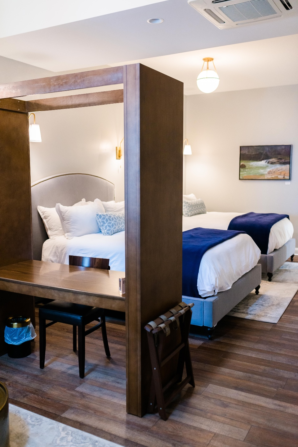 Places to Stay: The Colonial Inn in Hillsborough NC |The Colonial Inn Hillsborough NC by popular NC travel blog, I'm Fixin' To: image of two twin size beds with grey fabric covered head boards, white bedding, blue and white lumbar pillows and blue throw blankets.