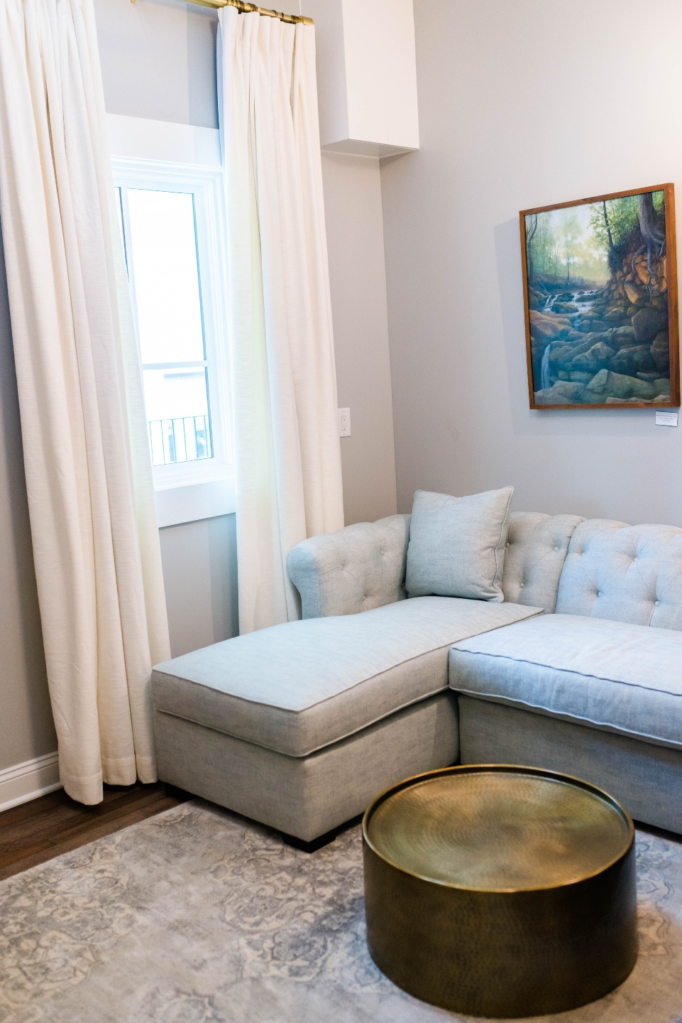 Places to Stay: The Colonial Inn in Hillsborough NC |The Colonial Inn Hillsborough NC by popular NC travel blog, I'm Fixin' To: image of a grey sectional couch and round gold coffee table next to a window with white drapes.