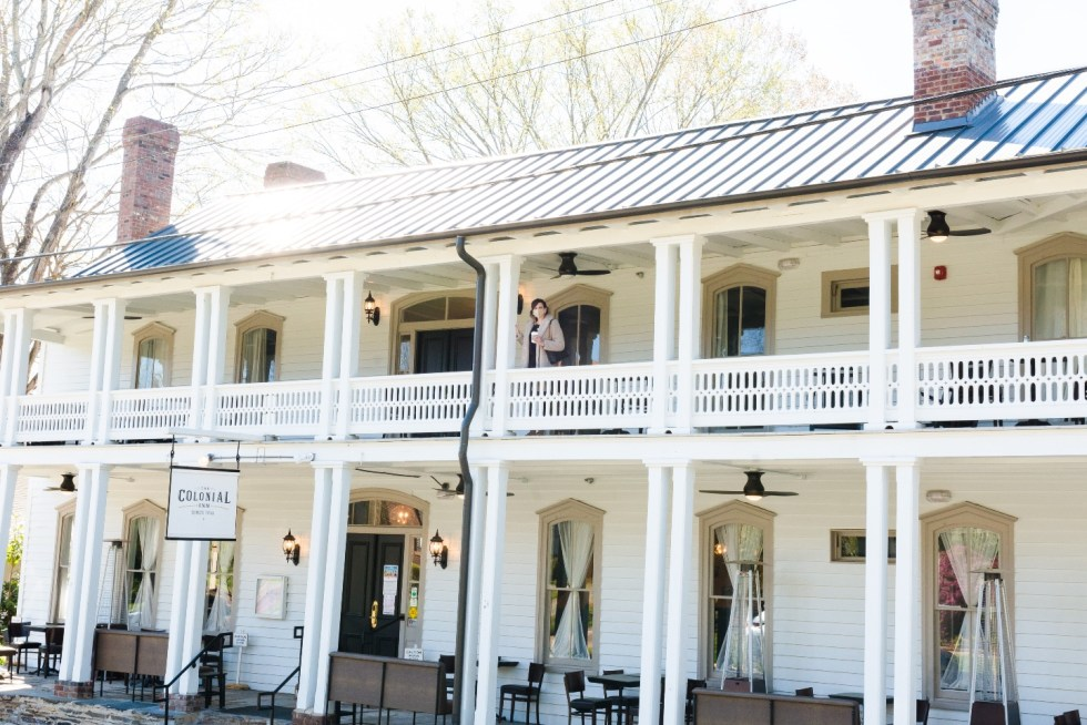 Places to Stay: The Colonial Inn in Hillsborough NC - I'm Fixin' To - @imfixintoblog | The Colonial Inn Hillsborough NC by popular NC travel blog, I'm Fixin' To: image of a woman standing outside at the The Colonia Inn in Hillsborough NC.