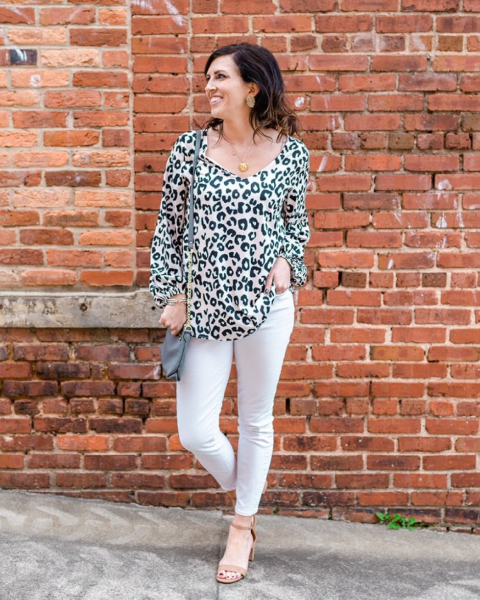 Spring Essentials by popular NC fashion blog, I'm Fixin' To: image of a woman standing in front of a brick wall and wearing a leopard print sweater and white jeans with tan block heel sandals.