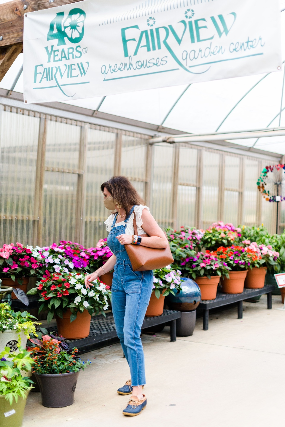 5 Spring Planting Tips with Fairview Garden Center - I'm Fixin' To - @imfixintoblog |Best Plants to Plant in Spring by popular NC lifestyle blog: image of a woman looking at potted plants at the Fairview Garden Center.