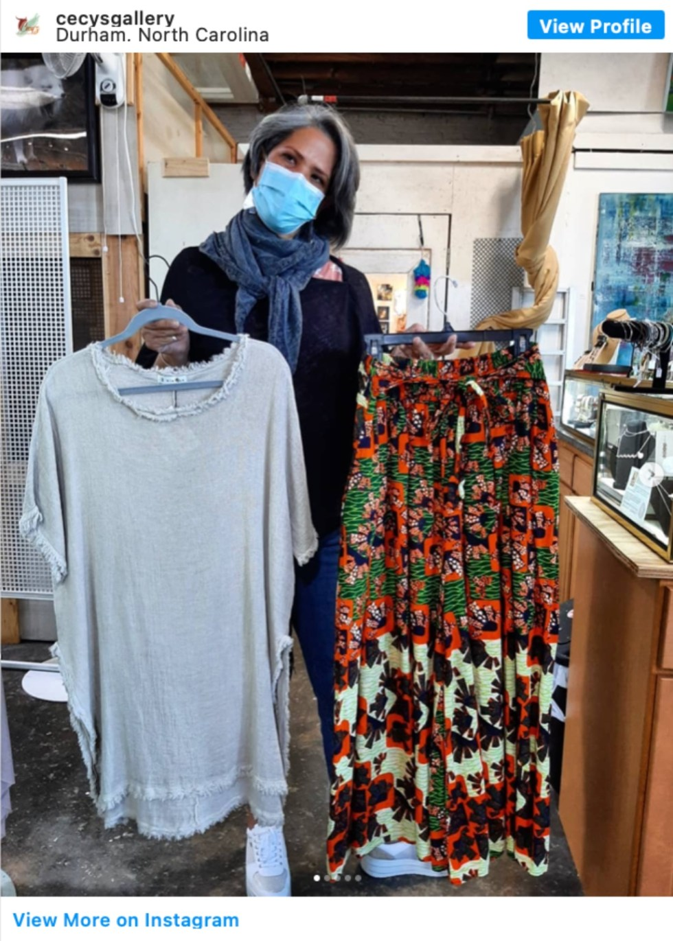 Durham Shopping: Top 11 Best Fashion Boutiques to visit After a Year of Quarantine - I'm Fixin' To - @imfixintoblog | Durham Shopping by popular NC lifestyle blog, I'm Fixin' To: image of a woman holding a frayed hem tunic and floral print midi skirt.