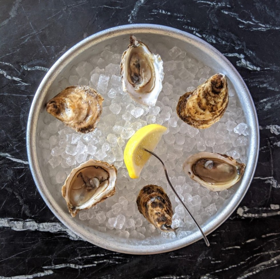 Raleigh Oyster Crawl: a Complete Guide to the Best Local Oyster Bars - I'm Fixin' To - @imfixintoblog | Raleigh Oyster Crawl by popular North Carolina blog, I'm Fixin' To: image of oysters on ice in a round metal pan.