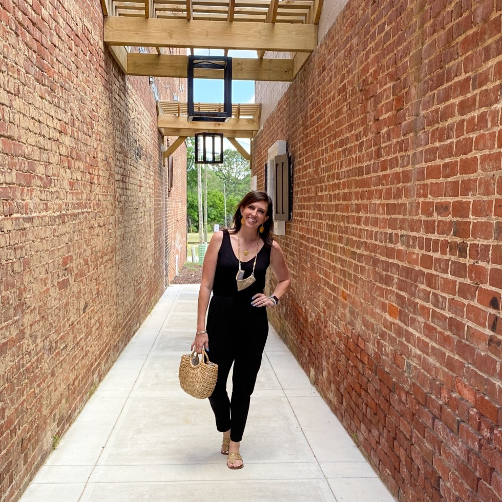 An Afternoon Trip to Franklin County, NC - I'm Fixin' To - @imfixintoblog | Franklin County NC by popular North Carolina travel blog, I'm Fixin' To: image of a woman standing in a walkway between two brick building and wearing. black jumpsuit and holding a woven straw handbag.