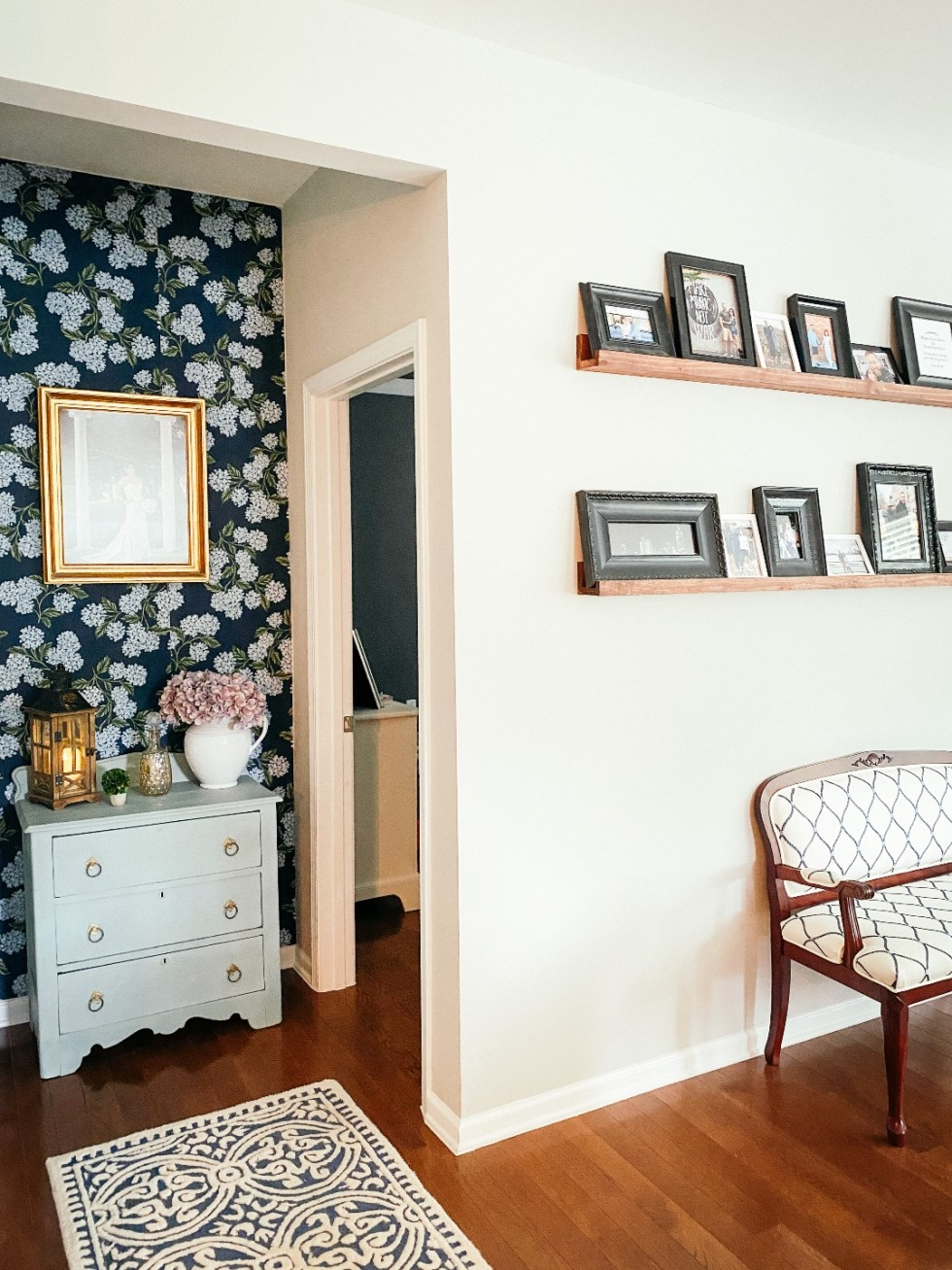 Room Reveal: Blue and Gray Living Room Ideas - I'm Fixin' To - @imfixintoblog | Blue and Grey Living Room Ideas by popular NC life and style blog, I'm Fixin' To: image of a living room decorated with a blue and white rug runner, floating wood shelves with black picture frames, white pillar candles, wooden picnic basket, blue and white floral wallpaper, blue and white armchair, and light blue dresser.