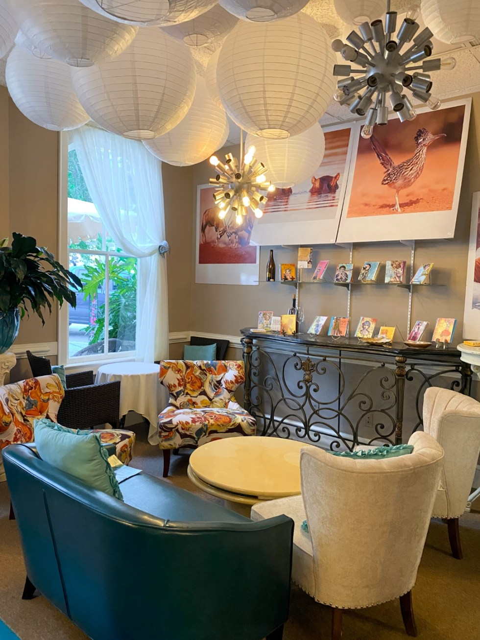 Top 10 Best Things to Do in Edenton, NC: A Complete Travel Guide - I'm Fixin' To - @imfixintoblog | Edenton Travel Guide by popular NC travel guid, I'm Fixin' To: image of a sitting are with white paper lanterns, blue leather couch, and sitting chairs.