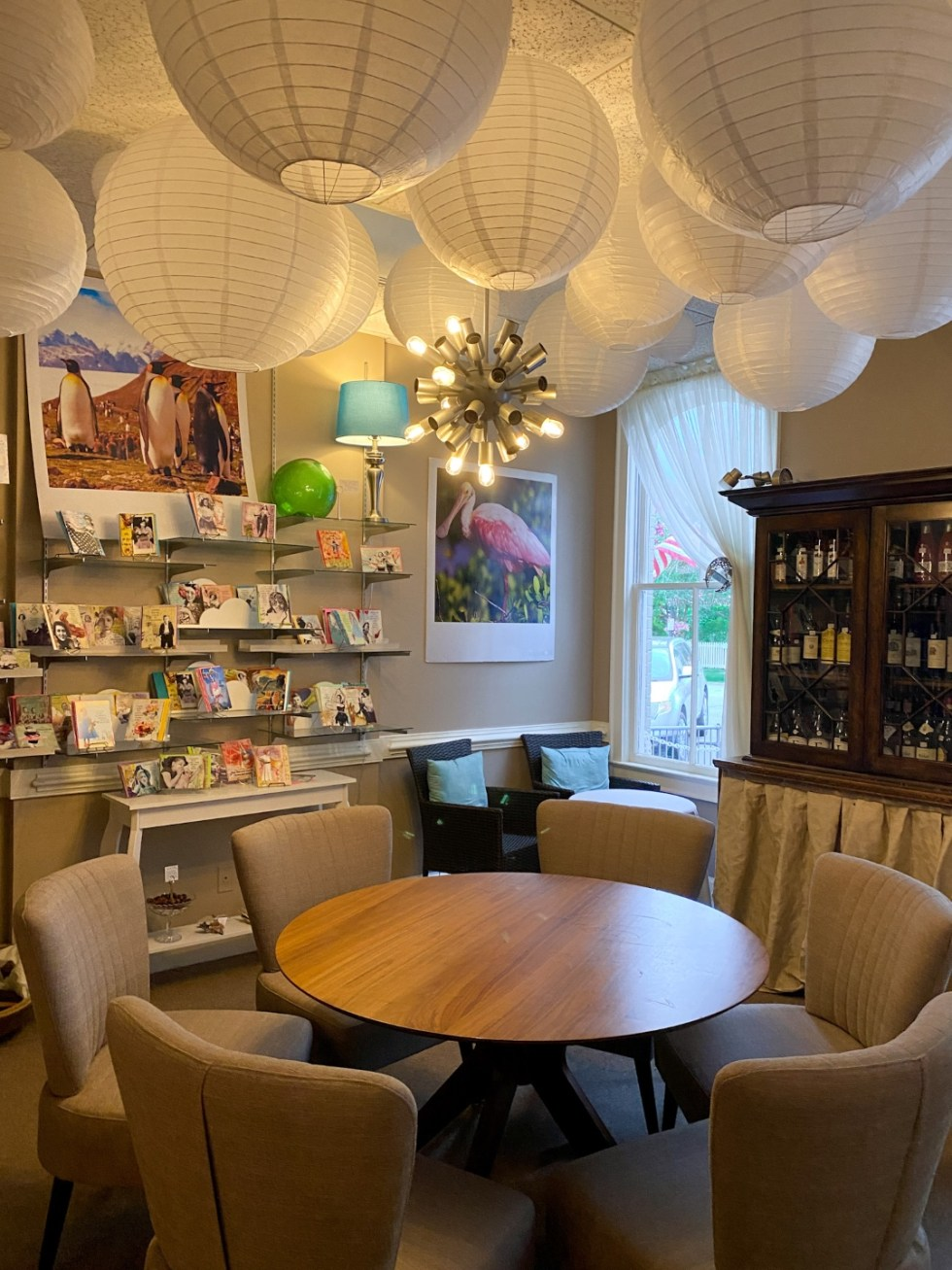 Top 10 Best Things to Do in Edenton, NC: A Complete Travel Guide - I'm Fixin' To - @imfixintoblog | Edenton Travel Guide by popular NC travel guid, I'm Fixin' To: image of white paper lanterns, liquor cabinet, round table with tan fabric chairs.