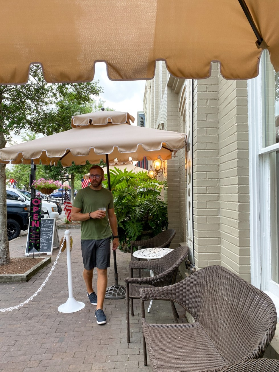 Top 10 Best Things to Do in Edenton, NC: A Complete Travel Guide - I'm Fixin' To - @imfixintoblog | Edenton Travel Guide by popular NC travel guid, I'm Fixin' To: image of a man standing next to the Edenton Bay Trading Company building.