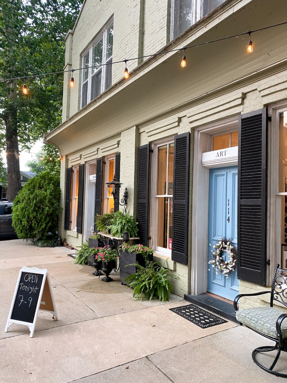 Top 10 Best Things to Do in Edenton, NC: A Complete Travel Guide - I'm Fixin' To - @imfixintoblog | Edenton Travel Guide by popular NC travel guid, I'm Fixin' To: image of a grey brick art gallery building with a light blue door and black shutters.