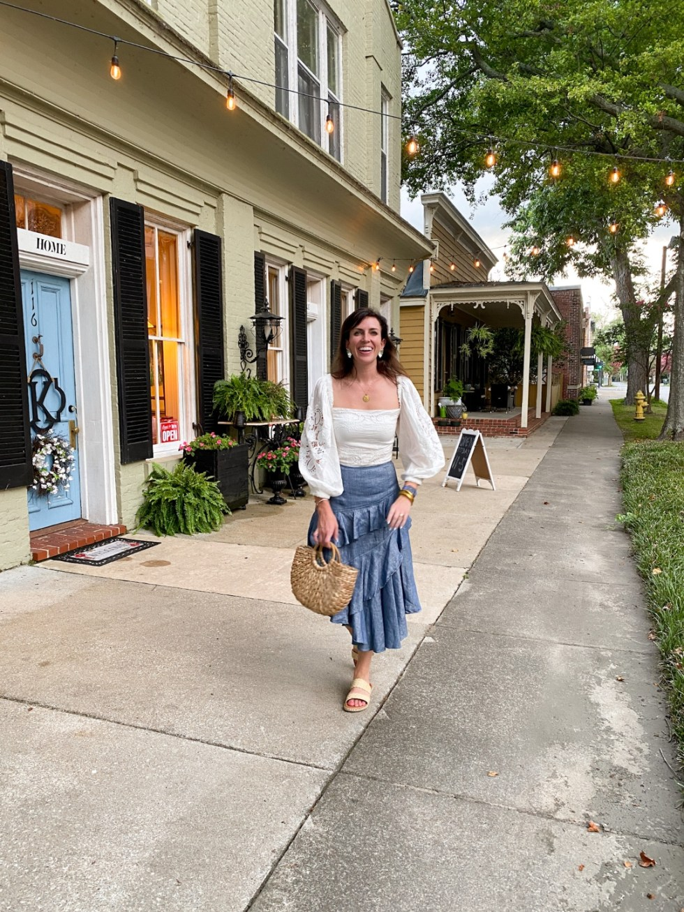 Top 10 Best Things to Do in Edenton, NC: A Complete Travel Guide - I'm Fixin' To - @imfixintoblog | Edenton Travel Guide by popular NC travel guid, I'm Fixin' To: image of a woman standing in front of a cream brick building with black shutters and a light blue door.