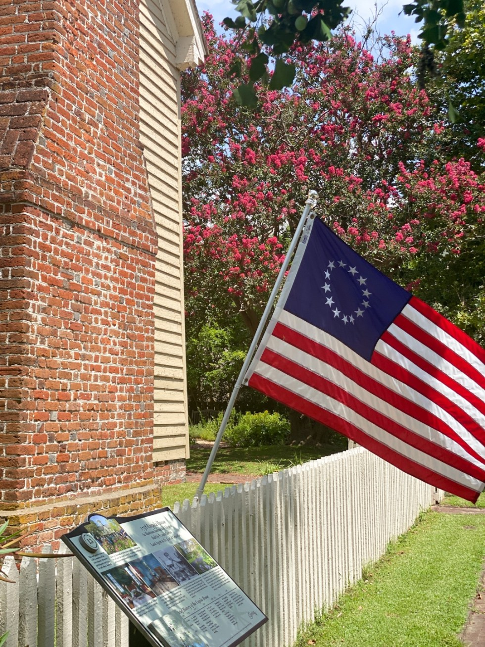 Top 10 Best Things to Do in Edenton, NC: A Complete Travel Guide - I'm Fixin' To - @imfixintoblog | Edenton Travel Guide by popular NC travel guid, I'm Fixin' To: image of a colonial flag next to a historical sign.