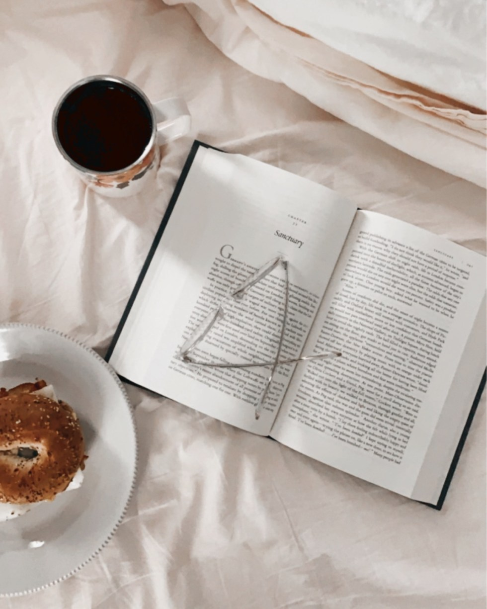 2021 Reading List: What I've Read So Far - I'm Fixin' To - @imfixintoblog | 2021 Reading List by popular NC lifestyle blog, I'm Fixin' To: image of an open book with a pair of glasses resting on top next to a plate containing a bagel sandwich.
