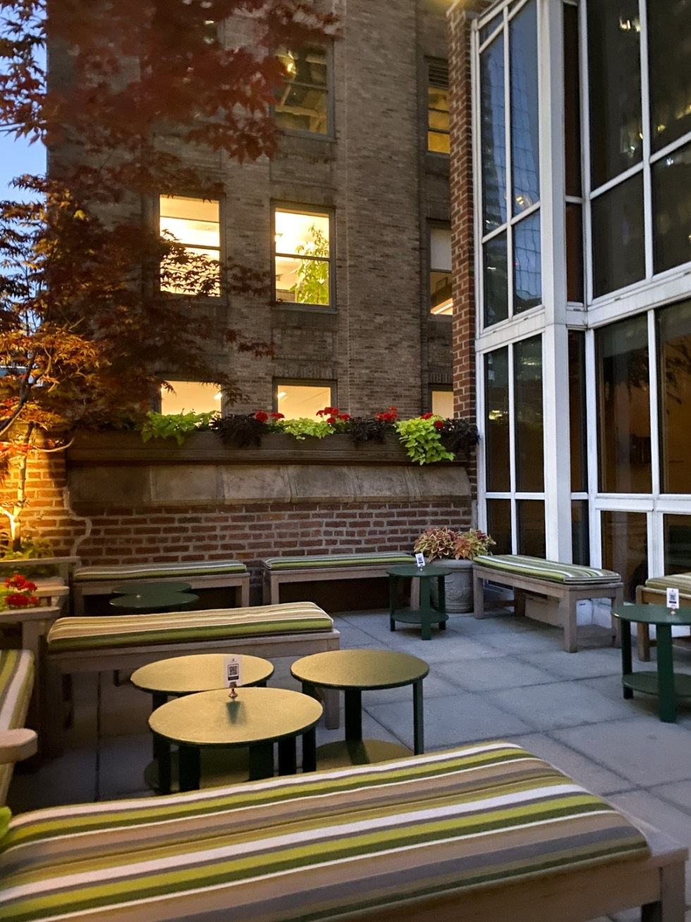 NYC Summer Weekend: Things to Do in NYC in the Summer - I'm Fixin' To - @imfixintoblog   NYC Summer Weekend by popular NC travel blog, I'm Fixin' To: image of a patio with round black coffee tables and wooden benches with tan and green stripe cushions.
