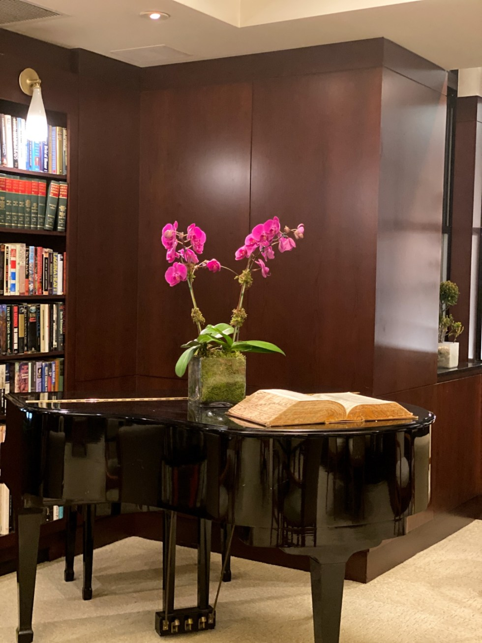 NYC Summer Weekend: Things to Do in NYC in the Summer - I'm Fixin' To - @imfixintoblog   NYC Summer Weekend by popular NC travel blog, I'm Fixin' To: image of a black baby grand piano with some pink orchids resting on top in a clear glass vase.