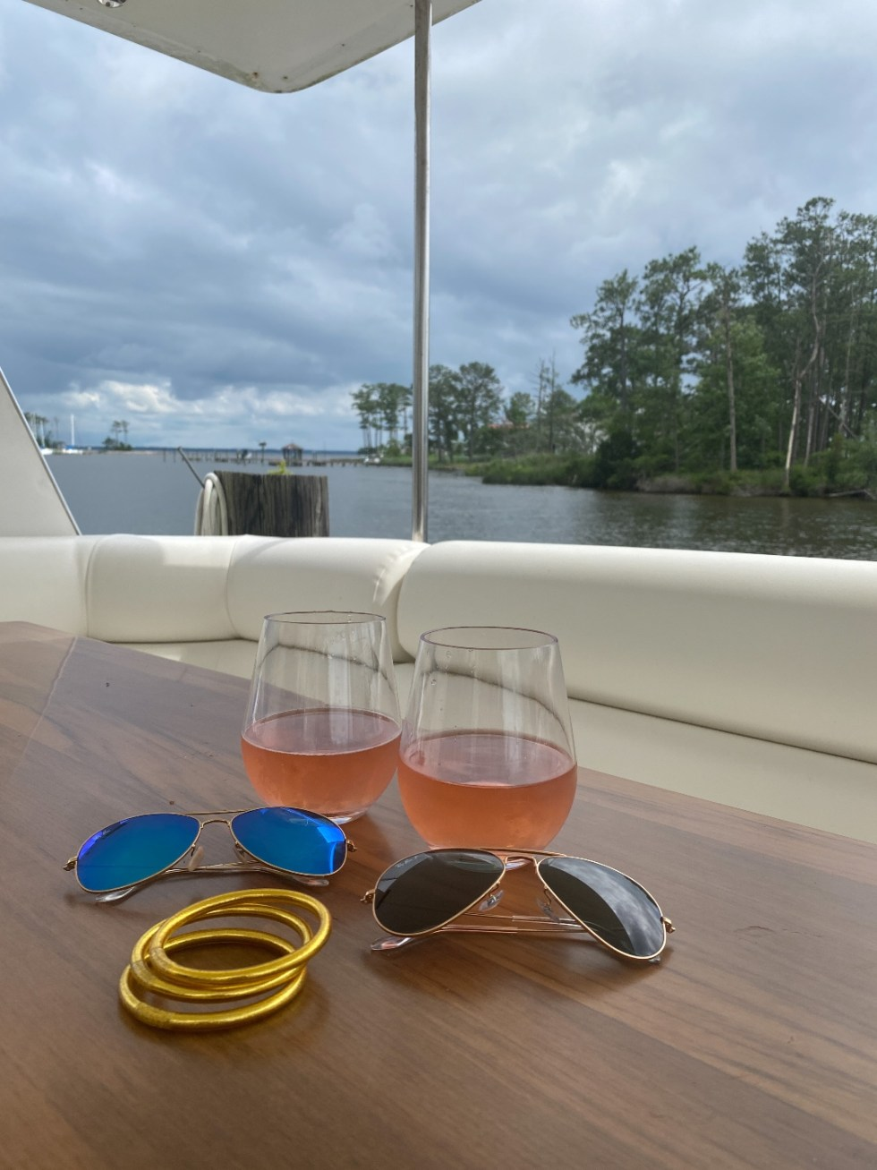 What to Do in Oriental, NC - I'm Fixin' To - @imfixintoblog | Things to do in Oriental NC by popular NC travel blog, I'm Fixin' To: image of two stemless wine glasses filled with rose wine next to two pairs of aviator sunglasses.