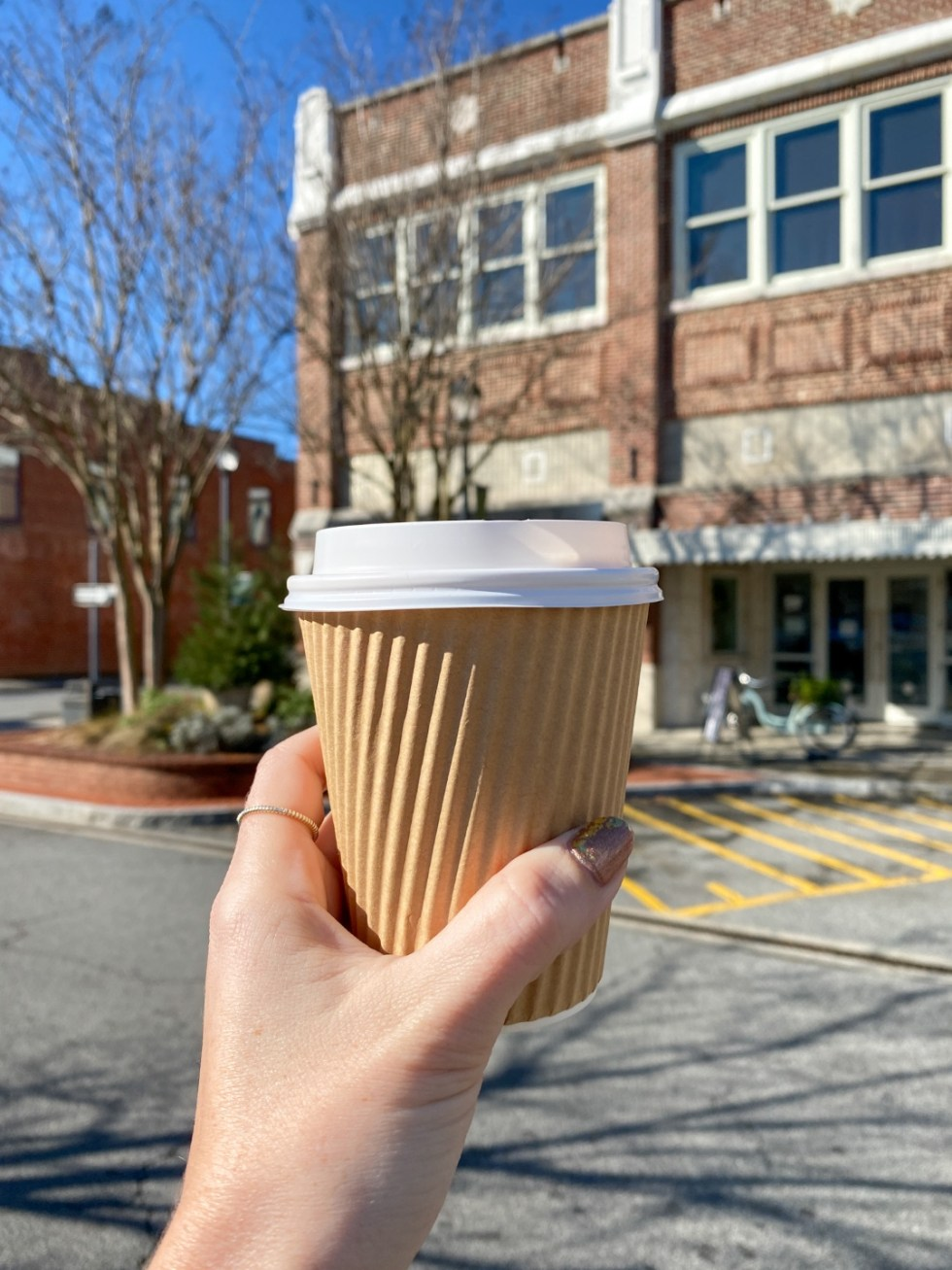 An Update on My North Carolina 100 County Tour - I'm Fixin' To - @imfixintoblog | Things to do in North Carolina by popular NC travel blog, I'm Fixin' To: image of a woman holding a cup of coffee.