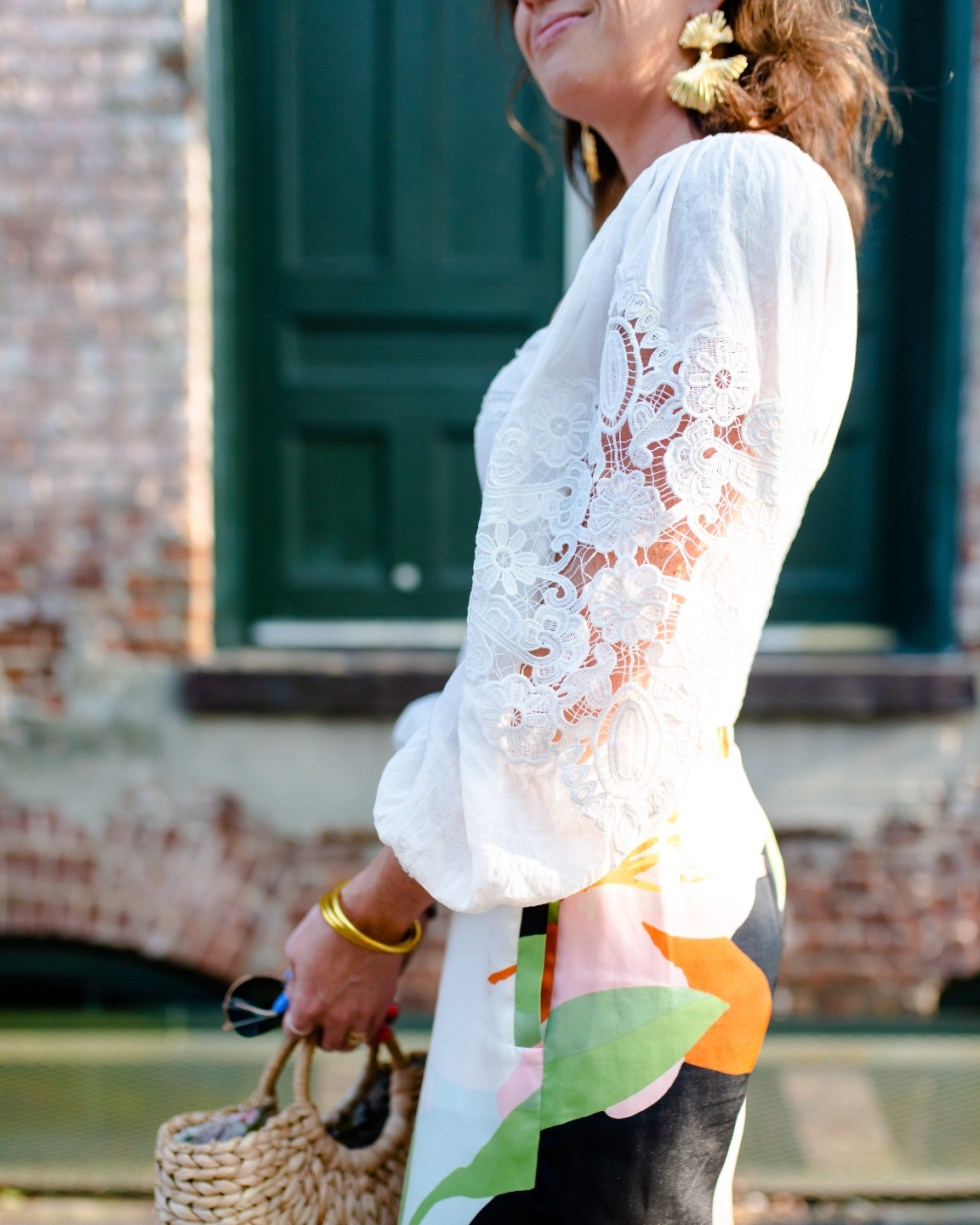White After Labor Day by popular NC fashion blog, I'm Fixin' To: image of a woman wearing. white lace sleeve top with a abstract design skirt and gold statement earrings.