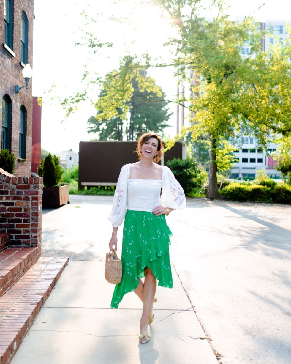 White After Labor Day by popular NC fashion blog, I'm Fixin' To: image of a woman wearing a white puff sleeve top with a green ruffle hem skirt and gold bow accent sandals.