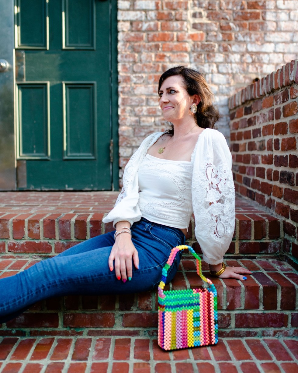 White After Labor Day by popular NC fashion blog, I'm Fixin' To: image of a woman wearing a white puff sleeve top and jeans while siting on some brick steps.