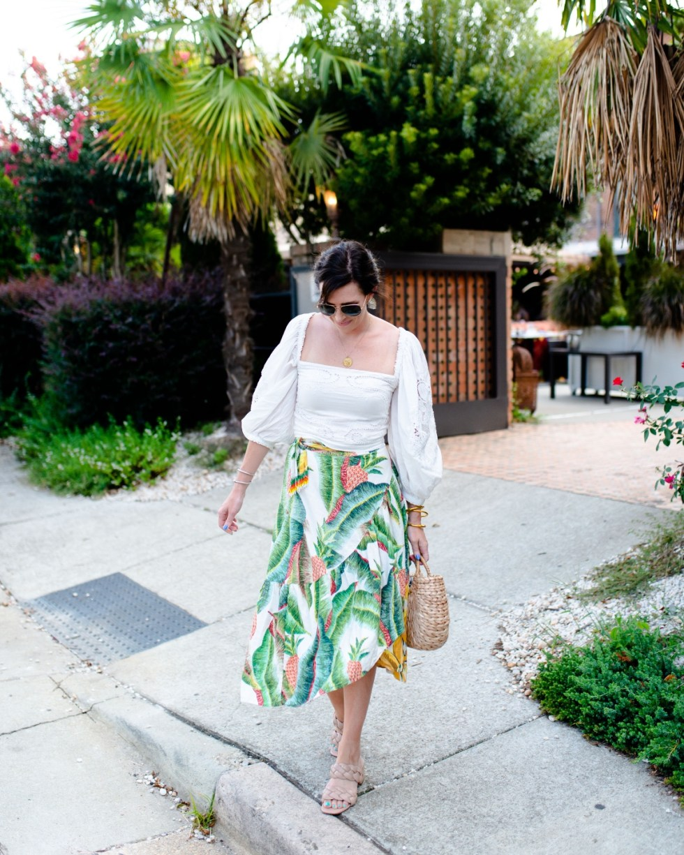 White After Labor Day by popular NC fashion blog, I'm Fixin' To: image of a woman wearing a  white puff sleeve top and banana leaf print skirt with tan braided strap handles.