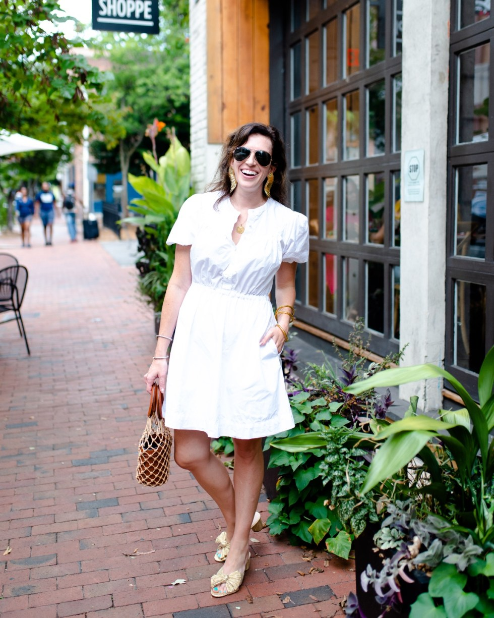 White After Labor Day by popular NC fashion blog, I'm Fixin' To: image of a woman wearing a white dress with gold bow accent sandals, gold statement earrings, and aviator sunglasses.