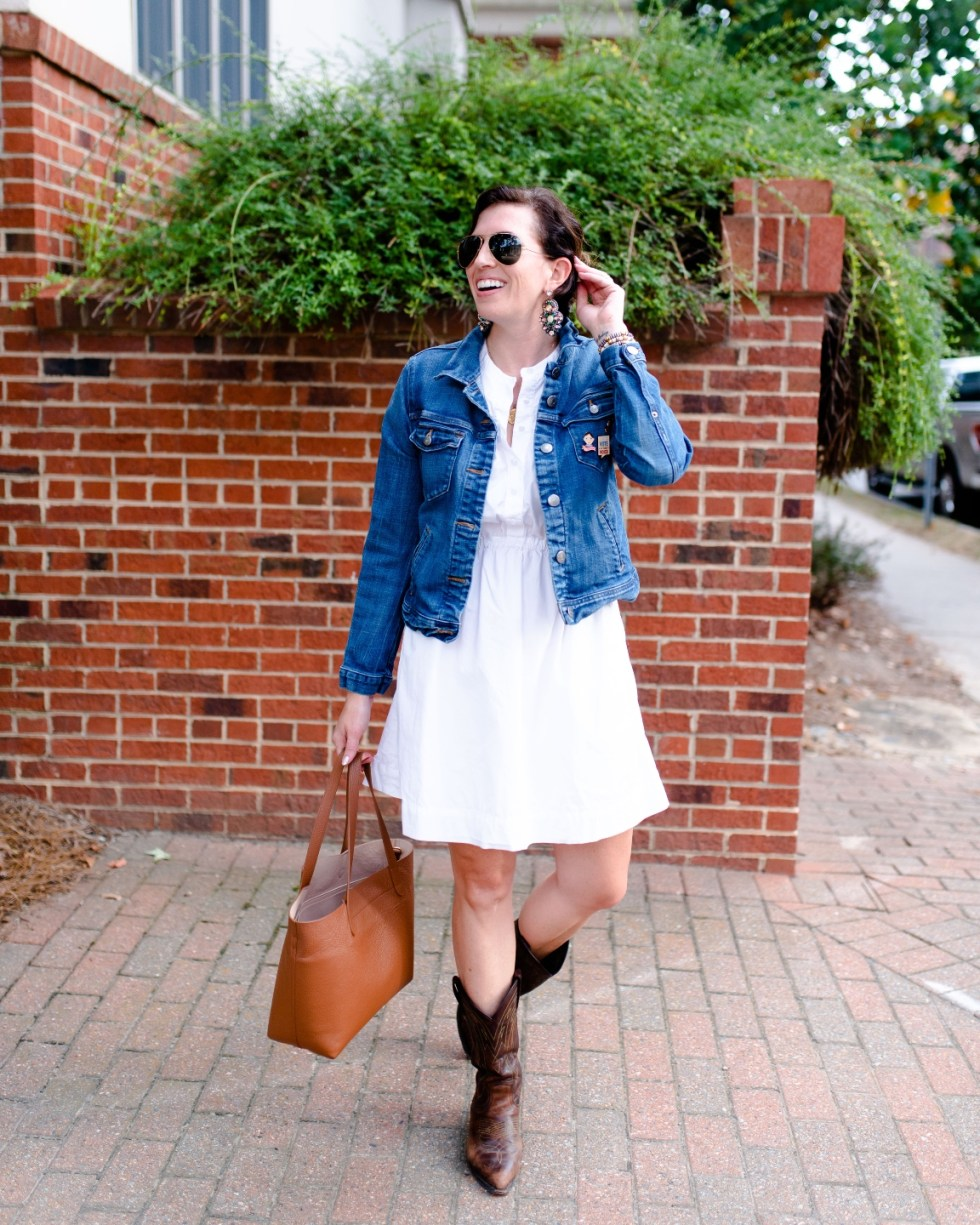 White After Labor Day by popular NC fashion blog, I'm Fixin' To: image of a woman earring a white dress with a jean jacket, brown cowboy boots, gold accent earrings, and holding a brown tote bag.