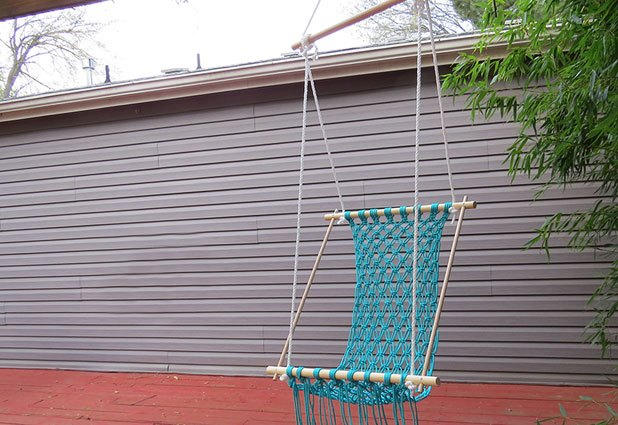 Hang the hammock from a sturdy hook and adjust the ropes.
